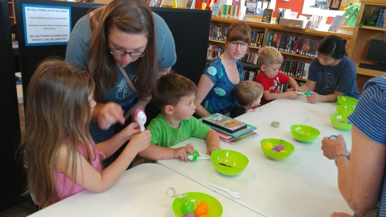 moms and a library volunteer assist budding musicians in our maraca factory
